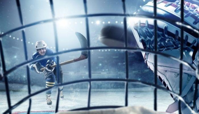 Vue depuis l'intérieur d'une visière de hockeyeur avec un joueur qui envoie la rondelle.